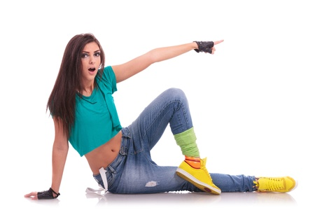 young woman street dancer laying on the floor, pointing amazed to her side while looking at the camera photo