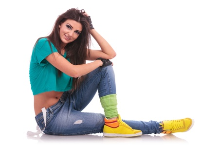 urban dance: modern woman dancer laying on the floor with legs crossed looking at the camera, on white background Stock Photo