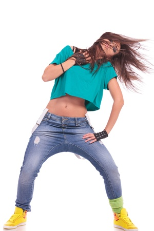 modern woman dancer posing with head tilted and hair flying, on white background photo