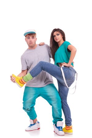 goofing: couple of young hip hop dancers fooling around. the man is holding the womans leg and looking at the camera. isolated on white