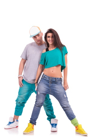 full length picture of a hip hop couple posing man behind smiling woman and looking at the camera photo
