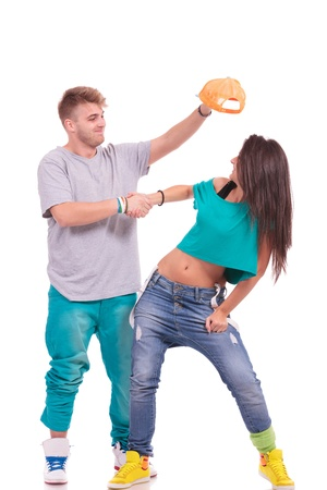 hip hop couple, man trying to put his hat on the womans head while shaking hands...goofing around on white background photo