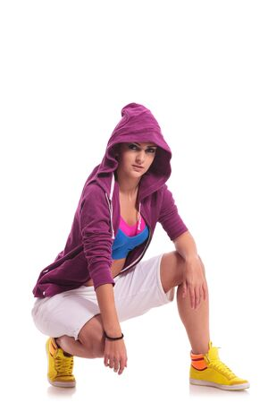 portrait of a young woman hip hop dancer sitting in a crouched position and looking at the camera photo