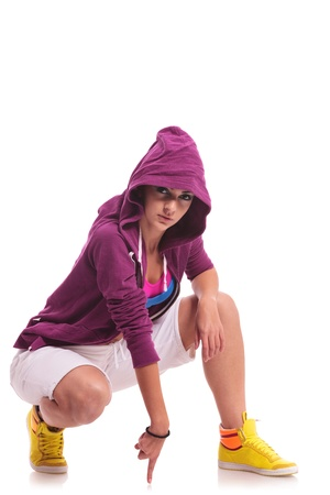 young hip hop woman dancer wearing a hoodie, posing crouched and touching the floor with index finger and looking at the camera photo