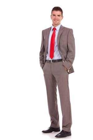 relaxed business man:  young business man standing with his hands in the pockets