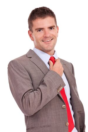 adjusting: young business man adjusting his tie and smiling to the camera Stock Photo