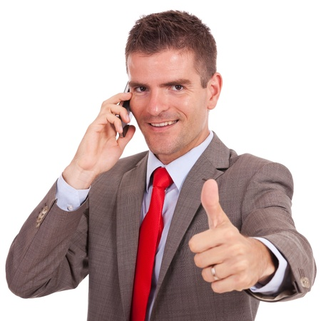 smiling young business man talking on the phone and making ok gesture. Isolated on white background photo
