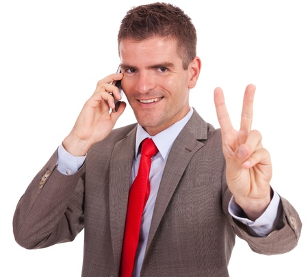 happy young business man speaking on the phone and showing victory sign to the camera Stock Photo - 16193501