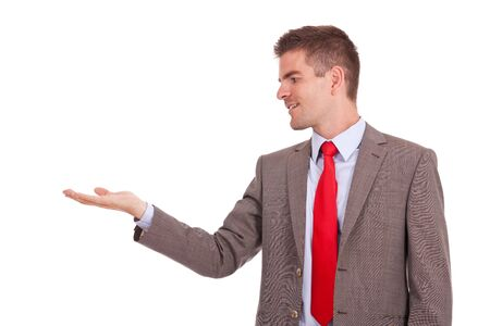 young business man holding something imaginary in his hand and looking at it. isolate on white background  photo
