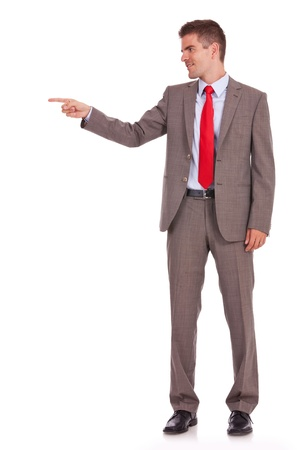 Side view, full length of a business man pointing at copyspace isolated over white background  photo