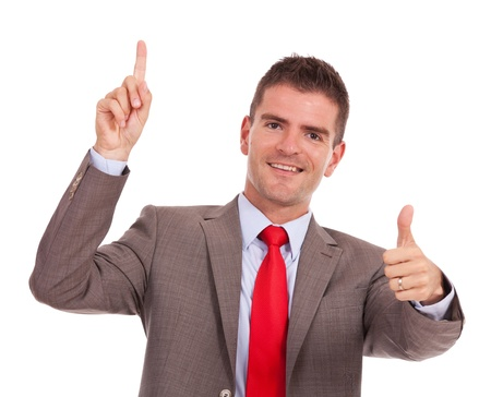 agree: young business pointing something above his head and showing thumbs up gesture, while smiling at the camera