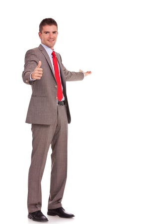 indicate: Portrait of young business man presenting something and gesturing thumbs up