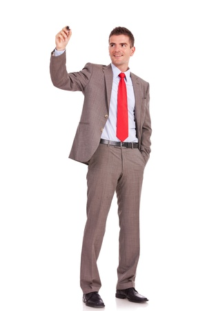 body writing: full body picture of a business man writing with marker and holding a hand in his pocket isolated on white background