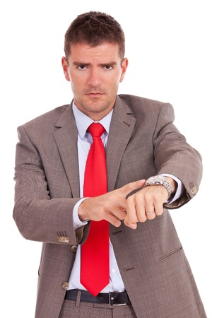 impatient: Angry business man pointing at his watch. Isolated on white.  Stock Photo