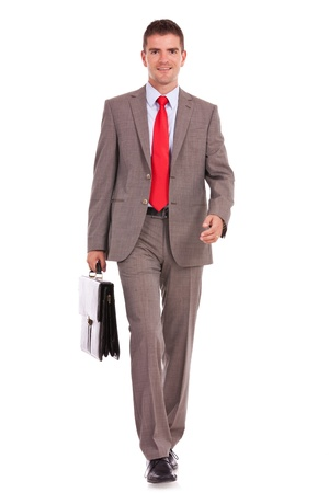 smiling young business man is walking with a briefcase against a white background Stock Photo - 16193436