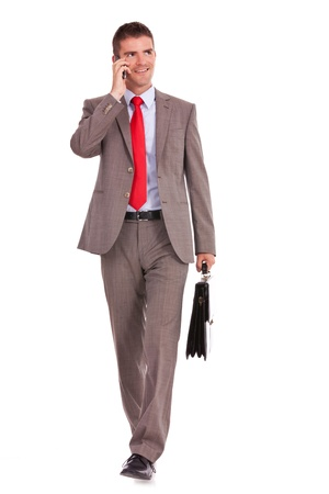 walking young business man with briefcase , looking away from the camera while speaking on his hone, isolated on white background  photo