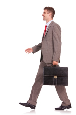 side view of a business man with briefcase walking and smiling, isolated on white Stock Photo - 16193437