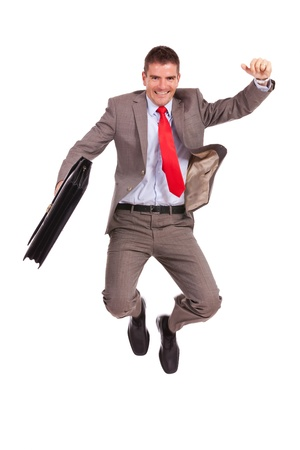 cheer full: very happy young business man holding a briefcase and jumping of joy on white background