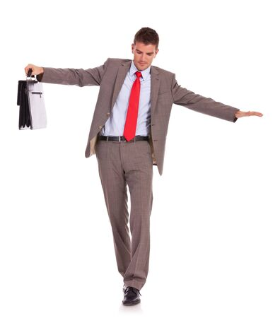 slowly: Business man with briefcase slowly walking with fear from falling, isolated on white