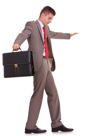 inconstant: side view of a young business man holding a briefcase balancing and walking forward on an imaginary rope