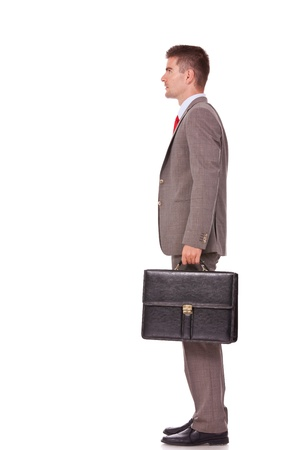certitude: side view portrait of young business man holding briefcase in hand isolated on white