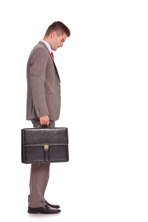 man looking down: side view of a young business man holding a briefcase and looking down - full body picture  Stock Photo