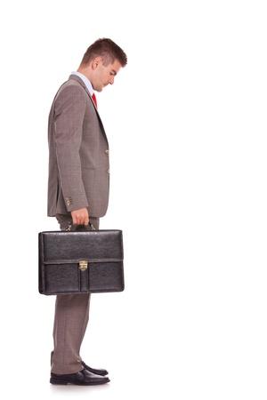 naar beneden kijken: zijaanzicht van een jonge zakenman met een koffer en naar beneden te kijken - full body foto