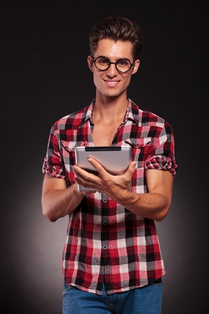 only man: happy young casual man wearing glasses working on a touchscreen tablet Stock Photo