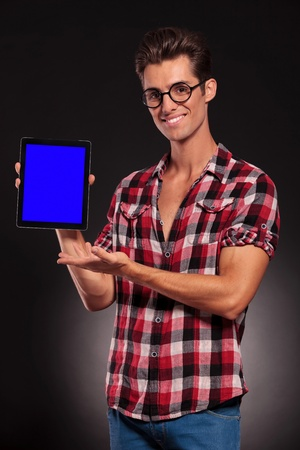 young casual fashion man presenting a new tablet pad on dark background photo