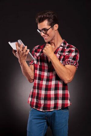side view of a fashion man reading on a tablet and winning  photo