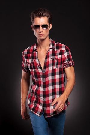 young fashion man wearing sunglasses walking forward on black background Stock Photo - 16334137