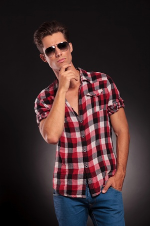 handsome fashion man wearing sunglasses and thinking on dark background photo