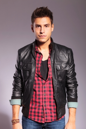 young man in leather jacket and jeans looking at the camera photo
