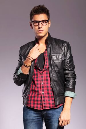 Portrait of young man with leather jacket and glasses against gray background Stock Photo - 16489778