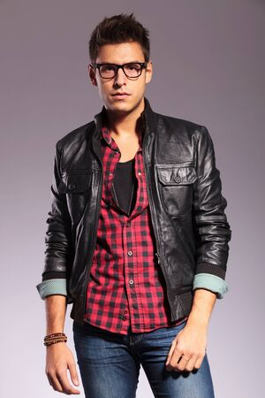 man with glasses: Handsome young man in a t-shirt, jeans and a leather jacket