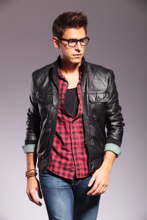 looking forward: walking casual man in leather jacket is looking to his side on gray background Stock Photo