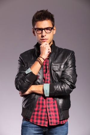 wearing glasses: portrait of a pensive young man with leather jacket and glasses