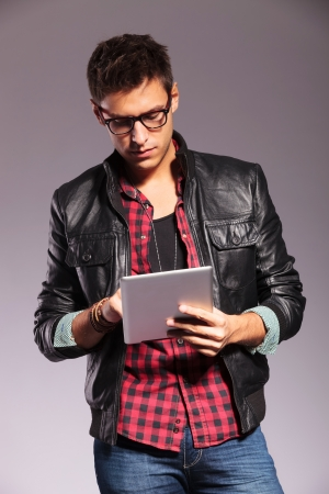 portrait of stylish casual man wearing leather jacket and glasses, working or reading on his tablet pad photo