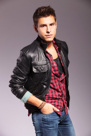 relaxed young casual man with hands in pockets and wearing leather jacket and jeans ongray background photo