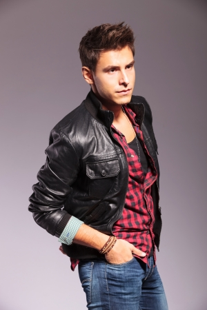 side view of a casual man in leather jacket looking away from the camera and standing with hands in pockets photo