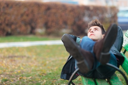 enjoy space: relaxed man on a bench in a park dreaming away