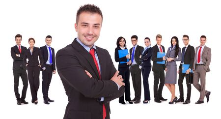 businessteam: young leader standing in front of his successful business team on white background