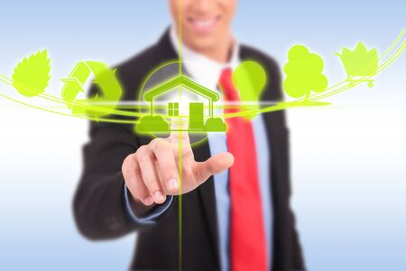 business man pushing a green house eco button Stock Photo - 17242372