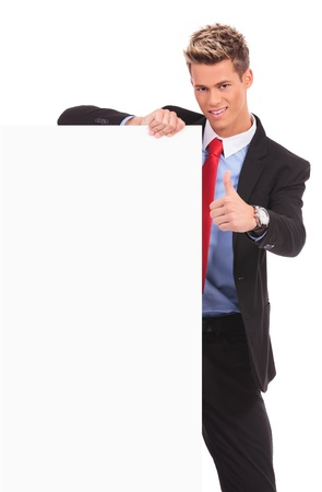Young business man with blank board making ok thumbs up gesture on white background  photo