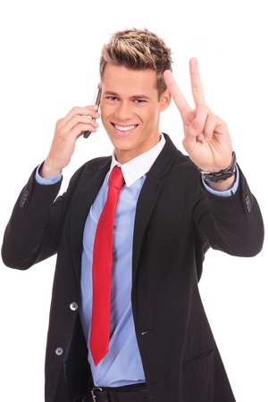 picture of a business man making victory sign while talking on the phone Stock Photo - 17242316
