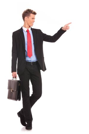 show case: Handsome young business man happy smile pointing finger to empty copy space, while holding a briefcase