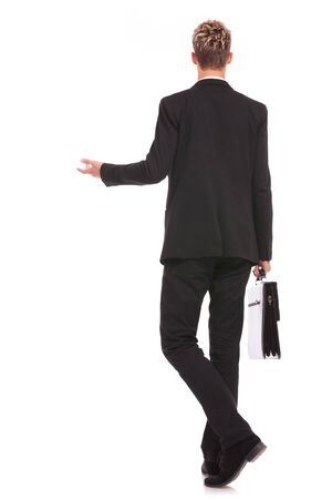 full body back view of a business man welcoming you on white background Stock Photo - 17242285