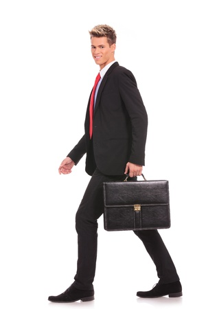 business man holding brief case and walking over white background  Stock Photo - 17242370