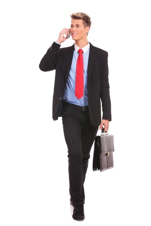 carying: Business man Walking forward and looking to a side while talking on the phone and carying a briefcase over white background  Stock Photo