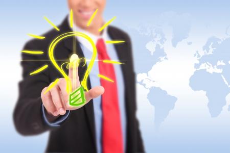 eficiencia energética: negocio sonriendo hombre que empuja un botón bombilla de luz que tiene una gran idea Foto de archivo